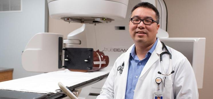 Physician stands in front of linear accelerator at PEI hospital